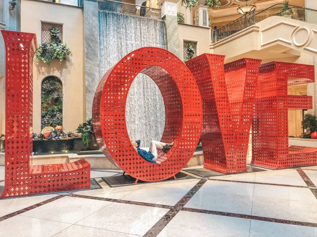 A woman laying down in the LOVE sign at the Venetian Las Vegas