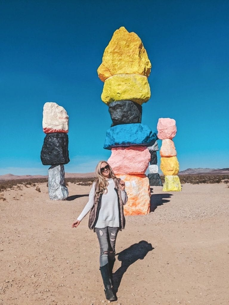 A woman in front of Seven Magic Mountains outside of Las Vegas, Nevada
