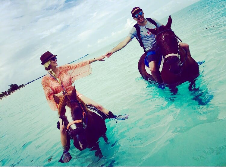 A couple riding horses in the ocean in Turks & Caicos
