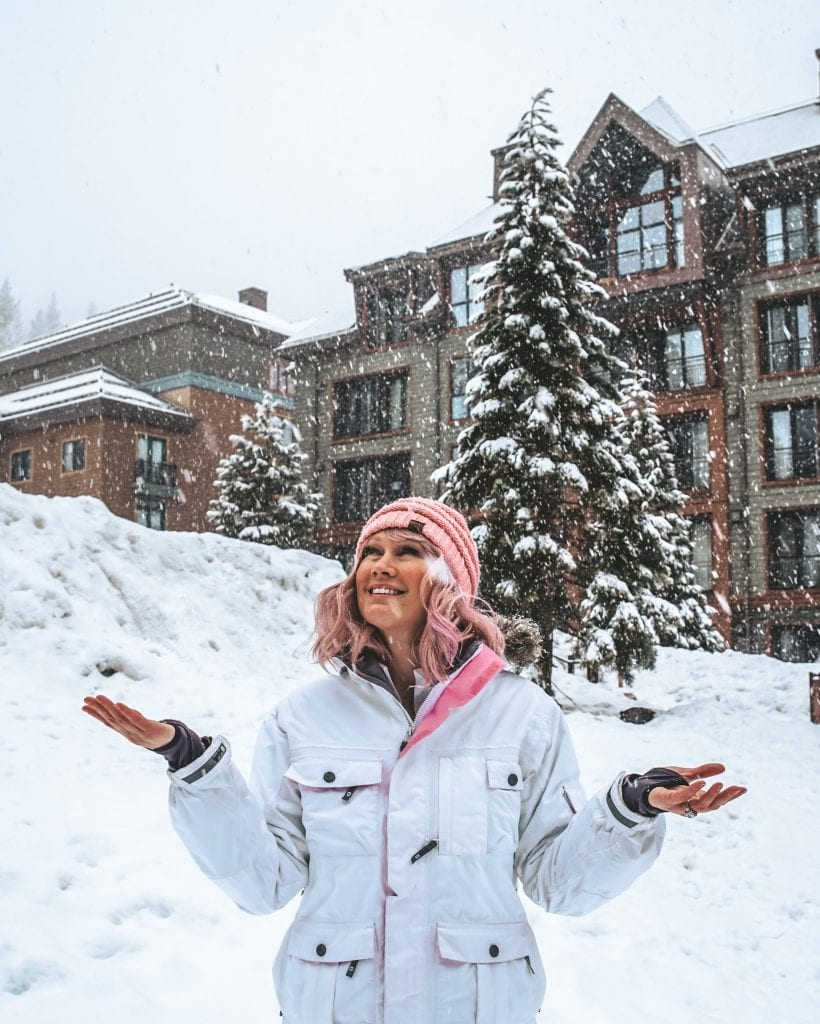 A woman standing in the falling snow at the Ritz Carlton Lake Tahoe